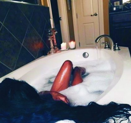 Izmir VIP escort girl lies in a bath naked, her slender wet feet can be seen above the water with a cap of foam and black hair beautifully lies on the edge of the bathtub, where she relaxes in the morning, she is waiting for her boyfriend who will brighten up her morning