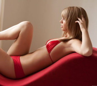 Izmir escort Erika is lying on the couch, sexy woman in red lying on a sofa in the profile of an attractive blond woman in red bikini resting on the couch almost without clothes