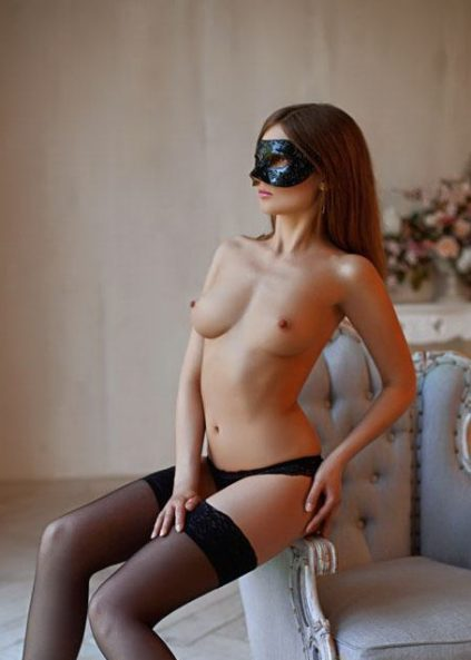Escort Izmir girl Olga sits on a chair, a seductive woman, a mysterious mask, fishnet beautiful stockings, long dark hair, a girl with a beautiful figure