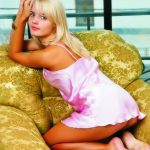 Izmir escort girl Lydia is sitting in a chair on her knees, she looks very perky and fun, her light gentle smile attracts attention, and long white hair looks very soft