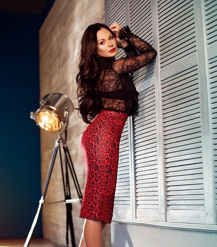 Escort girls in Izmir present woman Lana that is leaning against the black wall wearing body-tight skirt of the 'red snake' color that suits her
