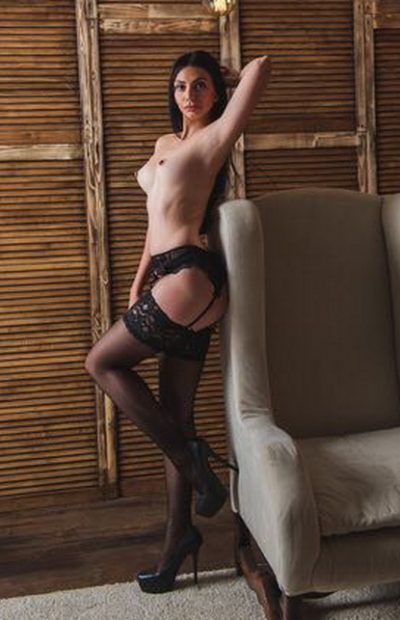 Escort girls Izmir present mistress Milena that is standing with the hand raised high above and is half-undressed