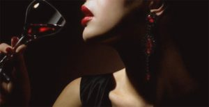 Izmir escorts girl is drinking wine in a seductive pose; scarlet lips are very sexy