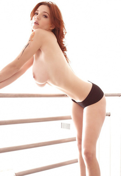 Girl in escort Lina stands on the same balcony topless and only being covered by her dark shorts, revealing us her interesting tattoo starting from a shoulder being of arm-length