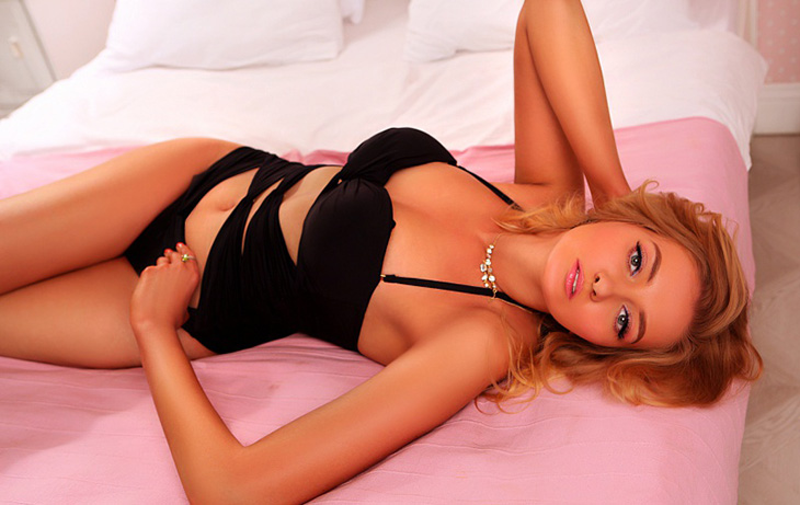 Izmir escort girl Lora is lying on the pinkish-clothed bed wearing all the same black swimming suit and looking at you with the desire