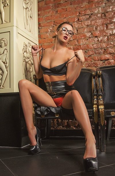 Escort Whatsapp superb lady Ariadna sits on a black leather chair exposing her chest by taking off the lacy bra