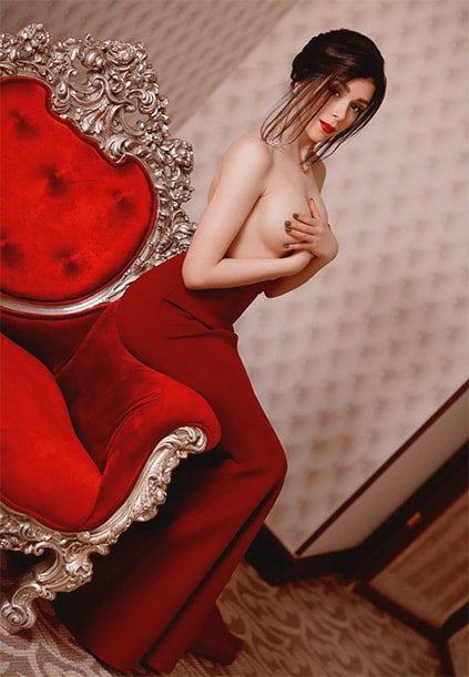 One of girls Izmir Marinka is sitting on the red furniture without her top covering boobs with her fingers