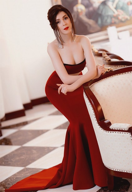 Girl Izmir Marinka is half-leaning to the chair in wonderful red dress having immaculate makeup on her face and showing an upper part of her breasts