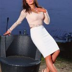 Escort Izmir Whatsapp chick Kirin is leaning against a street furniture making a smooth contrast between her white skirt, black seat, and young night