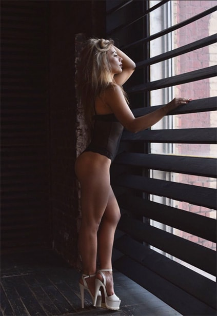 Escort Izmir Whatsapp splendid chick Ksiu is standing near the window looking into the distance dressed only in some cloth and high heels