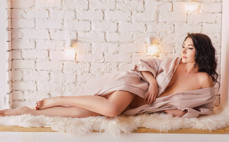 Ukrainian escort in Izmir is lying on the soft animal skin of white color giving a glance at her naked body only slightly covered with a bathrobe