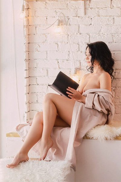 Ukrainian escort in Izmir Luisa is sitting reading a book wearing only a beige cloth
