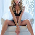 Izmir escort girl Amalia is in the chair with legs wide open and arms crossed at her pelvis' area