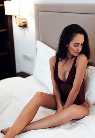 Izmir escorts incall Tanya is sitting on a white bed wearing black underwear, a bodysuit