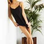 Blonde escorts Lyudmila is standing in black pulling her skirt down to cover a pussy