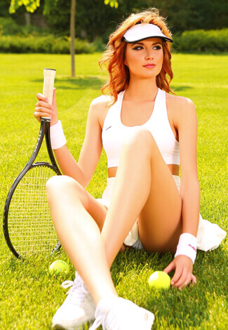 Izmir Rus eskortlar Ksenia is sitting on a green lawn holding a racket in a hand and unveiling panties