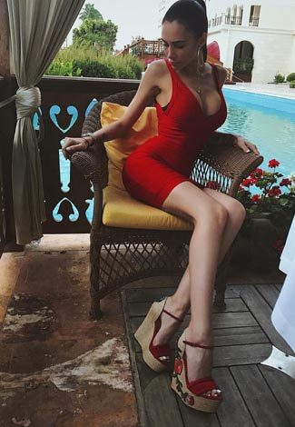 Outcall escort Lily wearing red body-tight dress is sitting on a chair nearby the pool