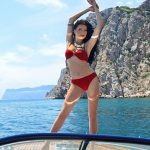 Izmir bayan eskortlar Valeria is at a yacht glowing with happiness in her sexy red swimsuit