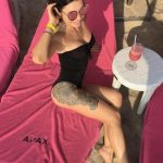 Escort agency Izmir Kira is on the beach wearing a black swimsuit and round sunglasses