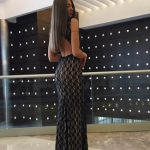Incall escort agency sweetheart Elena standing luxuriously dressed in the midst of a lobby