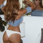 Incall escort agency girl Lesya stands in front of a mirror exposing her ass