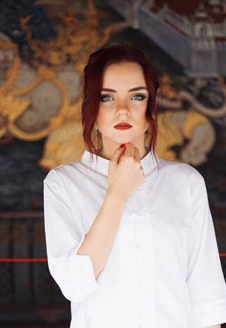 Izmir outcall escort Ksyusha is standing in the mid of the room wearing a white shirt