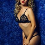 Mature blonde escort Vlada in the sexy black lingerie is leaning against the blue wall