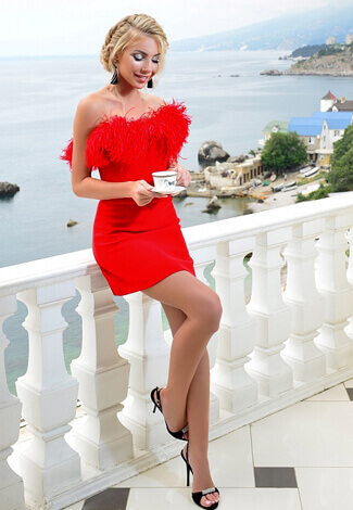 Izmir eskortlar girl Camilla in the red dress with fluff is on the background of the sea