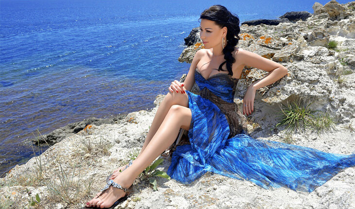 : Izmir bayan eskortlar Valeria is sitting on a cliff, which verges with the perfect blue sea