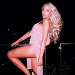 Blonde escort Alika is standing on a balcony exposing her left leg to our sight from the long dress