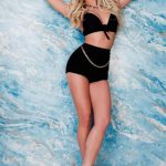 Izmir escort girl Amalia is standing pressing self against the wall, wearing high-waste attire